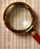 Looking through magnifying glass to financial report. — Stock Photo