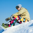 Snowboarder sitting on a ski slope. — Stock Photo