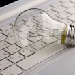 Light bulb and computer keyboard. — Stock Photo