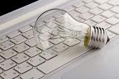 Light bulb and computer keyboard. — Stock Photo