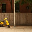 A court yard with a yellow vespa — Stock Photo