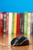 A computer mouse against books — Stock Photo