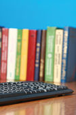 Keyboard lying on a desk with books — Foto Stock