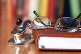 Close-up of a notebook, spectacles, stethoscope on the desk — Stock Photo