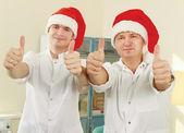 Happy doctors in red santa hat — Stockfoto