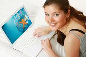Genç kız kanepe üzerinde bir dizüstü bilgisayar kullanarak — Stok fotoğraf