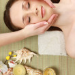 Young woman getting facial massage at spa salon — Stock Photo