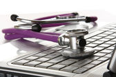 A violet stethoscope on a white laptop — Stok fotoğraf