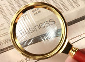 Magnifying glass on financial report — Stock Photo