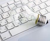 Light bulb and computer keyboard — Stock Photo