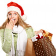 Young woman with Santa hat holding shopping bags — Stock Photo