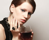 Young woman with a wineglass near the wall — Stock Photo