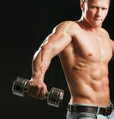 Bell'uomo muscoloso lavorando con manubri — Foto Stock