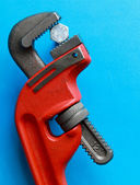 Closeup of adjustable wrench over blue. — Stock Photo