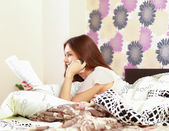 Teenager girl   on a bed reading a book and talking on   phone — Stock Photo