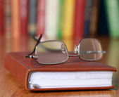 Book with glasses on the desk against books. — Stock Photo