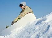 Snowboarder sitting on a ski slope. — Stock Photo