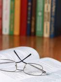 Livro com óculos sobre a mesa — Fotografia Stock