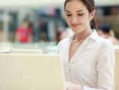 красивые счастливая женщина, сидящая с ноутбуком — Стоковое фото