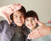 Couple making frame from fingers — Stock Photo