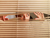 Woman looking through   blinds — Stock Photo