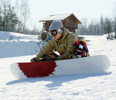 Snowboarder sitting on a ski slope — Stock Photo