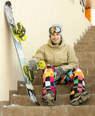 Snowboarder sitting on a ladder — Stock Photo