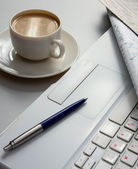 A cup of coffee, paper and a pen on a laptop — Stock Photo