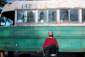 Man sitting in front of the Magic Bus — Stockfoto