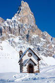 Small church in front of peak in Passo Rolle, Italy — Stock Photo
