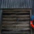 Red life ring hanging next to old wooden garage door — Stock Photo #38252299