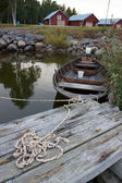 Wooden boat standing in pier tied with rope with red houses in background — Foto de Stock