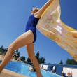 Stock Photo: Womwith towel runs near swimming pools