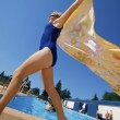 Womwith towel runs near swimming pools — Stock Photo #31604345