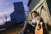 Hombre se sienta al lado de guitarra — Foto de Stock