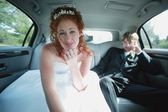 Bride Leans Forward In Car — Stock Photo