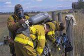 Fireman Adjusting Equipment On Partner — Stock Photo
