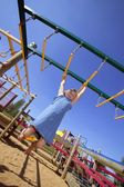 Child Swinging On Monkey Bars At Playground — Stock Photo
