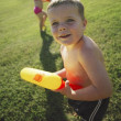 Stock Photo: Children Playing In Park With Water Pistols