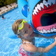 Stock Photo: Girl Playing In Swimming Pool With Inflatable Shark