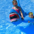 Stock Photo: Girls Playing In Swimming Pool With Inflatable Shark