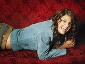 Attractive Woman Laying On Sofa And Laughing — Stock Photo