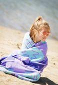 Dívka se nachází na pláži v ručníku — Stock fotografie
