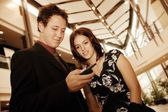 Professional Couple Looking At Cell Phone — Stock Photo