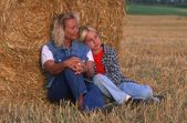 Mom And Daughter Relaxing In The Hayfield — Stock Photo