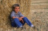Young Boy Sitting On Hay Bale — Stock Photo