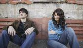 Junge trendige paar sitzt auf dem bürgersteig — Stockfoto