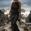 Beautiful Blonde WomWandering Along Rocky Seashore In Black Dress While Holding Dress Shoes — Stock Photo #31620941