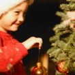 Girl Hanging Ornament On Christmas Tree — Stock Photo #31621417