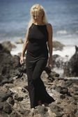 Beautiful Blonde Woman Wandering Along Rocky Seashore In Black Dress While Holding Dress Shoes — Stock Photo